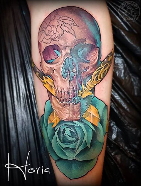 ArtCastleTattoo Tattoo ArtiestHoria Skull with two ornate gold daggers turquoise rose semi realism semi neo traditional full color tattoo Color