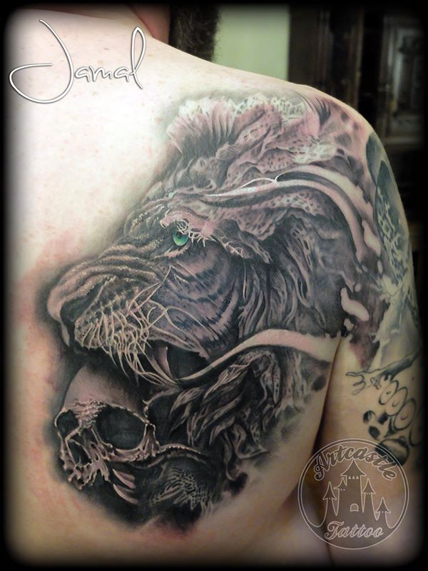 ArtCastleTattoo Tattoo ArtiestJamal Realistic lion with a skull in his mouth its part of a full sleeve with chest piece and back part. In progress... Black n Grey