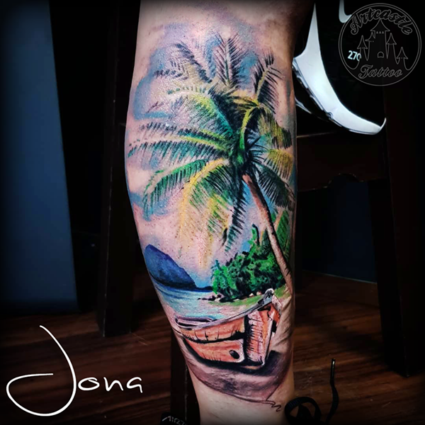 ArtCastleTattoo Tattoo ArtiestJona Realistic carribbean beach landscape tattoo with palm tree in full color lower leg Color